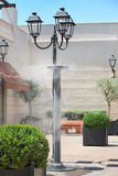 飞溅被汽化的水的喷水隆头在街道为了冷却热的夏天温度 免版税库存照片