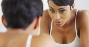 飞溅面孔用水和看在镜子的黑人妇女 免版税库存图片