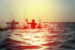 飞溅水的三个年轻人在海 免版税库存图片