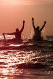 飞溅水的两个年轻人在海 库存图片