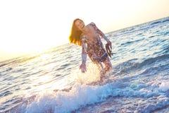 飞溅水的五颜六色的礼服的美丽的女孩在日落的海洋 免版税库存照片