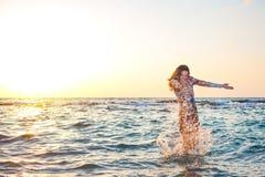 飞溅水的五颜六色的礼服的美丽的女孩在日落的海洋 图库摄影
