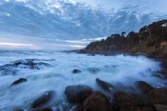 飞溅水的剧烈的海洋浪潮由岩石岸在日落期间在加利福尼亚 免版税库存照片
