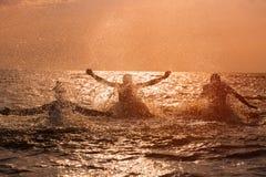 飞溅水的朋友在海在日落 免版税库存照片