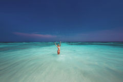 飞溅水的比基尼泳装的美丽的妇女在海 免版税库存图片