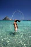 飞溅水的美丽的少妇与她的头发。 免版税库存照片