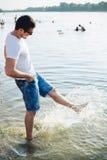 飞溅水的英俊的人 免版税库存照片