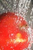 飞溅水的苹果 库存图片