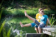 飞溅水的年轻夫妇在湖 免版税库存图片