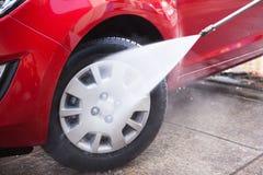 飞溅水的水管在黑轮胎 免版税库存图片