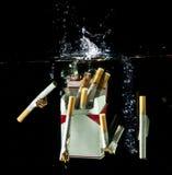 飞溅水的cigarretes 库存图片
