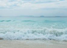 飞溅从蓝色海挥动到在缅甸的清楚的白色沙子海滩和Copyspace对输入文本 免版税库存图片