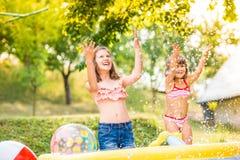 飞溅水,晴朗的夏天的两个女孩在庭院里 免版税库存照片