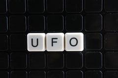 飞碟控制文本词标题说明标签盖子背景背景 字母表信件在黑反射性背景的玩具块 库存图片