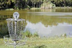 飞碟由一个湖的高尔夫球目标在公园 免版税库存图片