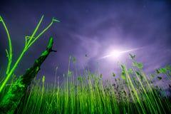 飞碟飞行发出光线-夜满月风景 库存图片