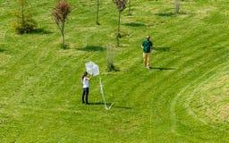 飞行一只白色风筝的男人和妇女在公园 库存照片