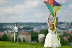 飞行一只风筝的新娘和新郎在一婚礼之日 免版税库存照片