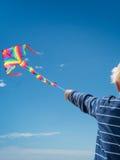 飞行一条个别线路风筝的年轻白肤金发的男孩 免版税库存图片