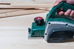 飞行与一个电整平机工具的木匠木表面 免版税图库摄影