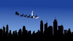 飞行与驯鹿的圣诞老人雪橇在夜甲晕的城市 皇族释放例证