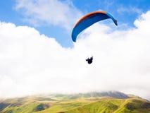 飞行与paramotors有美好的山景的滑翔伞反对蓝色多云天空 图库摄影