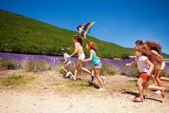 飞行五颜六色的风筝的愉快的孩子在夏天 免版税库存图片
