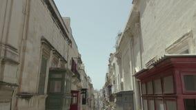 飞行今后举在狭窄的美丽的老街道,瓦莱塔,马耳他上的寄生虫 白色汽车击退 葡萄酒阳台 4K 股票视频