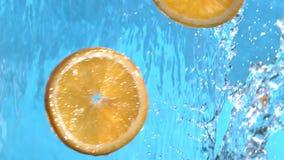 飞行入在慢动作的水小瀑布的新橙色切片射击了在1500 fps 股票录像