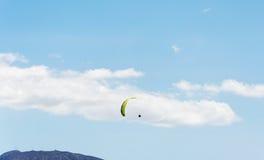 飞行到在山和蓝天背景的paraplene  免版税库存图片
