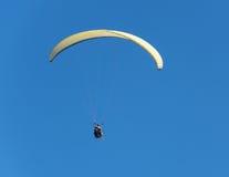 飞行到在无云的天气的paraplene在蓝色背景  免版税库存图片