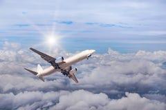 飞行到在白色上的高昂的高度的白色商业飞机覆盖与阳光 免版税库存图片
