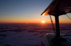 飞行双翼飞机在日落 免版税库存照片