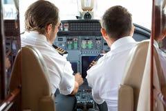 飞行员和副驾驶在私人喷气式飞机驾驶舱内 免版税库存图片