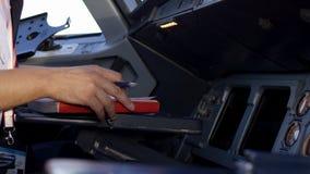 飞行员在平面驾驶舱内的检查仪器 公司喷气机飞行员运行的控制背面图  飞行员 免版税库存照片