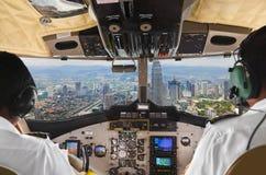 飞行员在平面驾驶舱和城市内 免版税库存照片