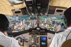 飞行员在平面驾驶舱和城市内 图库摄影