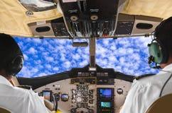 飞行员在平面驾驶舱和天空内 免版税库存照片