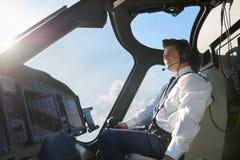 飞行员在直升机驾驶舱内在飞行期间的 免版税库存图片
