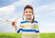 飞行员帽子的愉快的小男孩有飞机的 免版税库存图片