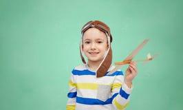 飞行员帽子的愉快的小男孩有飞机的 库存照片