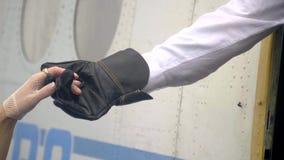 飞行员的人` s手握一只妇女` s手苗条手在帮助a的一副有花边的手套的减速火箭的服装的 影视素材