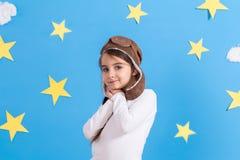 飞行员` s盖帽的小愉快的女孩微笑和使用,在白色衬衣的在演播室 蓝天、白色云彩和星 免版税库存图片