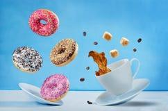 飞行咖啡与多彩多姿的油炸圈饼的 库存照片