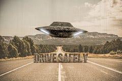 飞行在一条空的沙漠路的飞碟 库存图片