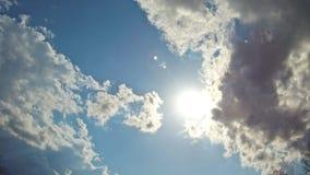 飞行在与太阳的蓝天的白色云彩发出光线行动背景 股票录像