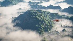 飞行在与杉树的山的红色飞机在云彩 免版税库存照片