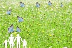 飞行在与绿色草甸背景福利救济概念的一个家庭的蓝色蝴蝶 库存图片