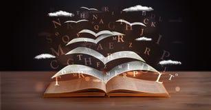 飞行在书外面的页和发光的信件 免版税库存照片