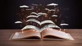 飞行在书外面的页和发光的信件 库存照片